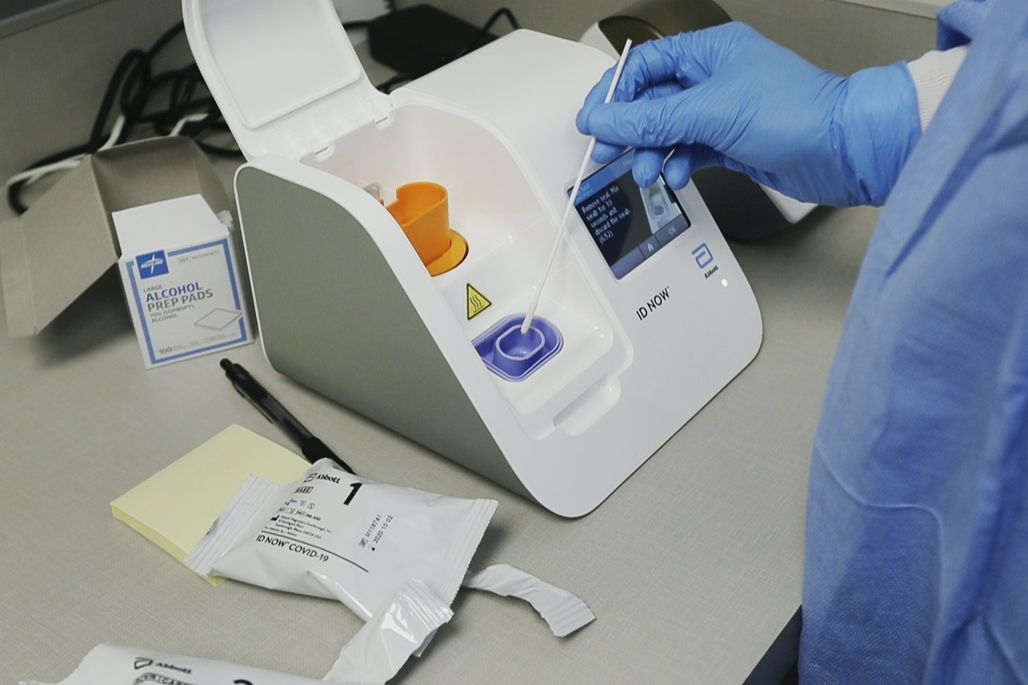 A lab technician using a swab to put a sample into a rapid test machine.