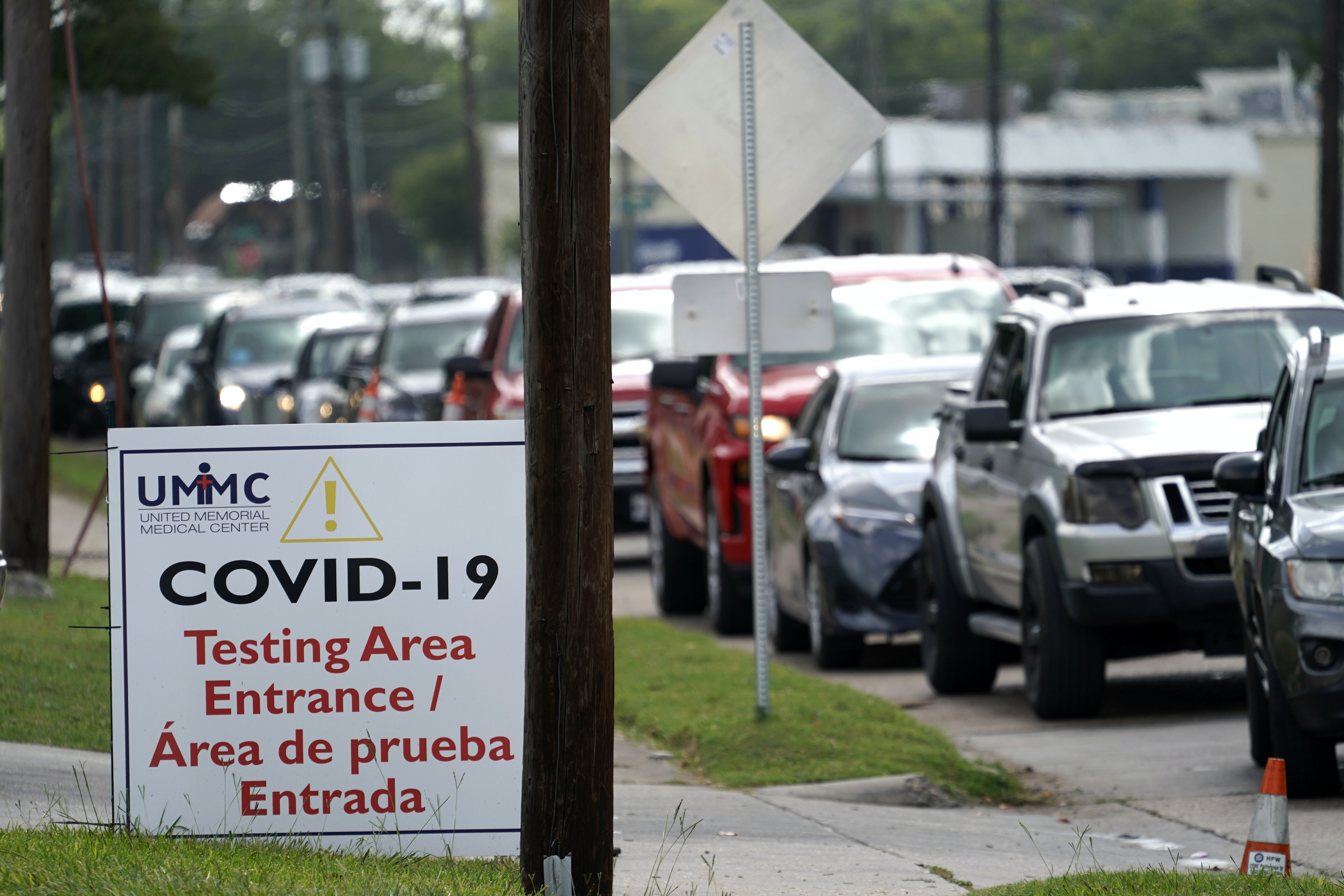 A line of people waiting in cars in front of a sign for COVID-19 testing.