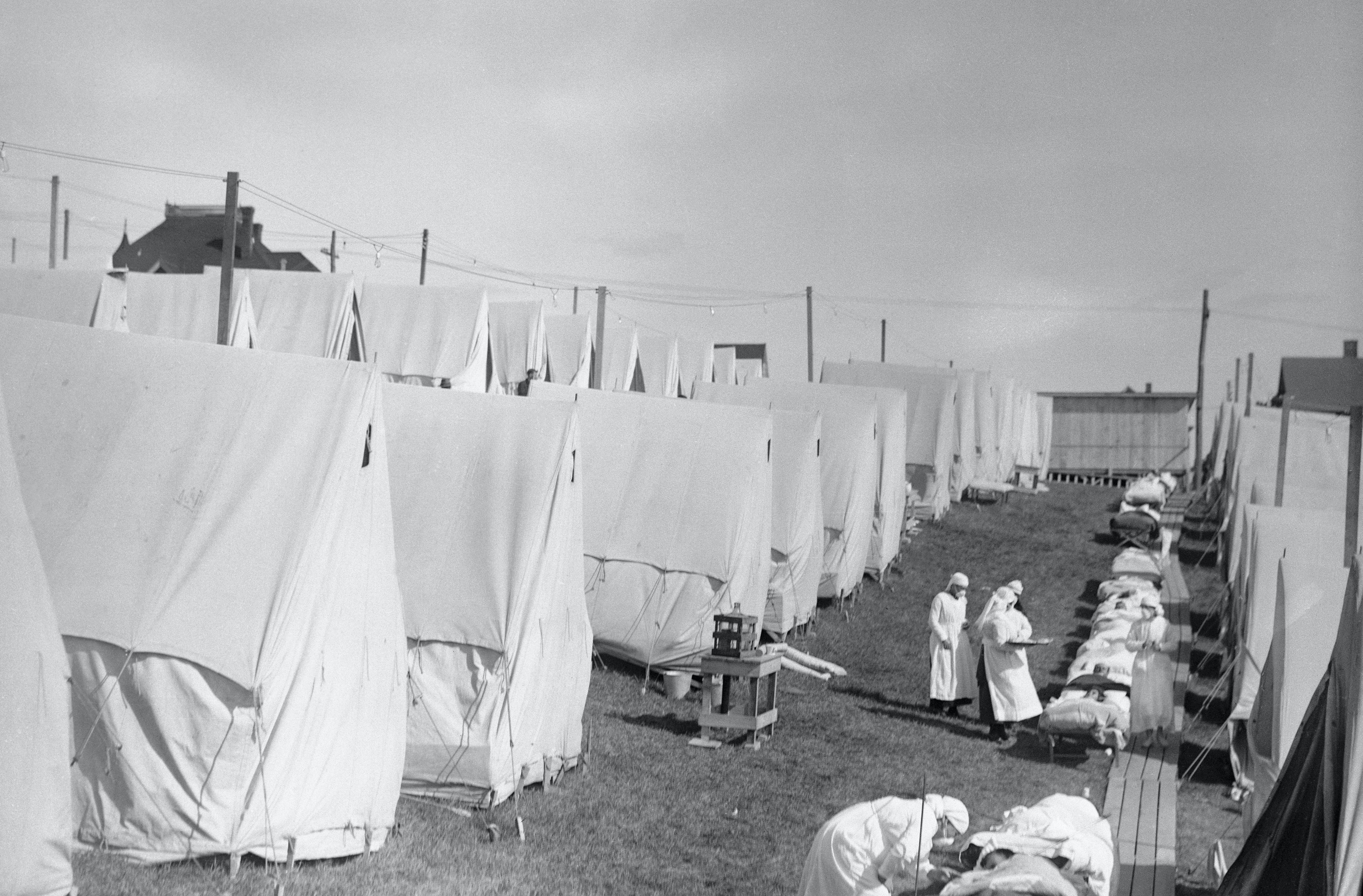 Patients lie on outdoor beds at flu camp filled with rows of tents.