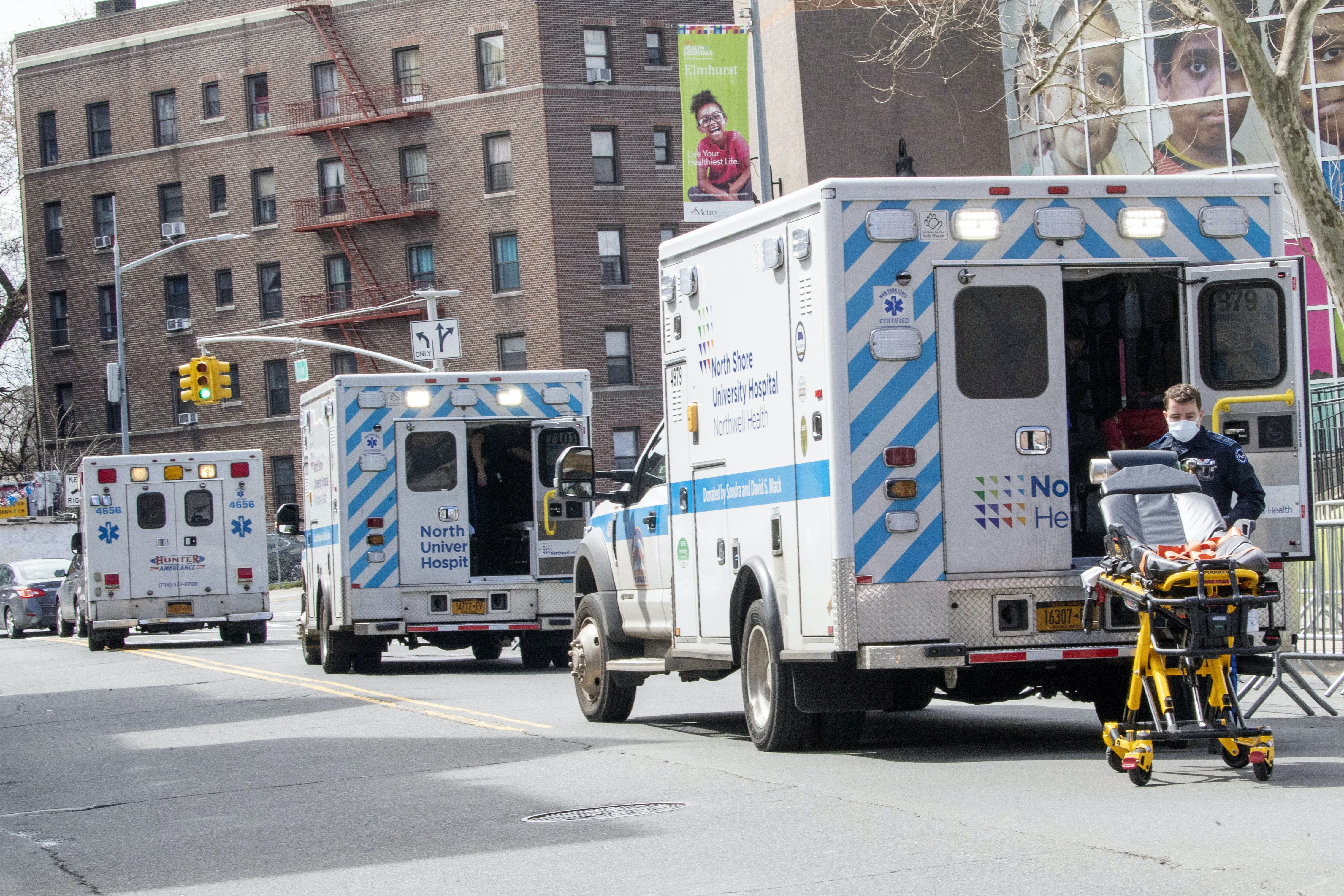 Three ambulances lined up in front of a hospital.