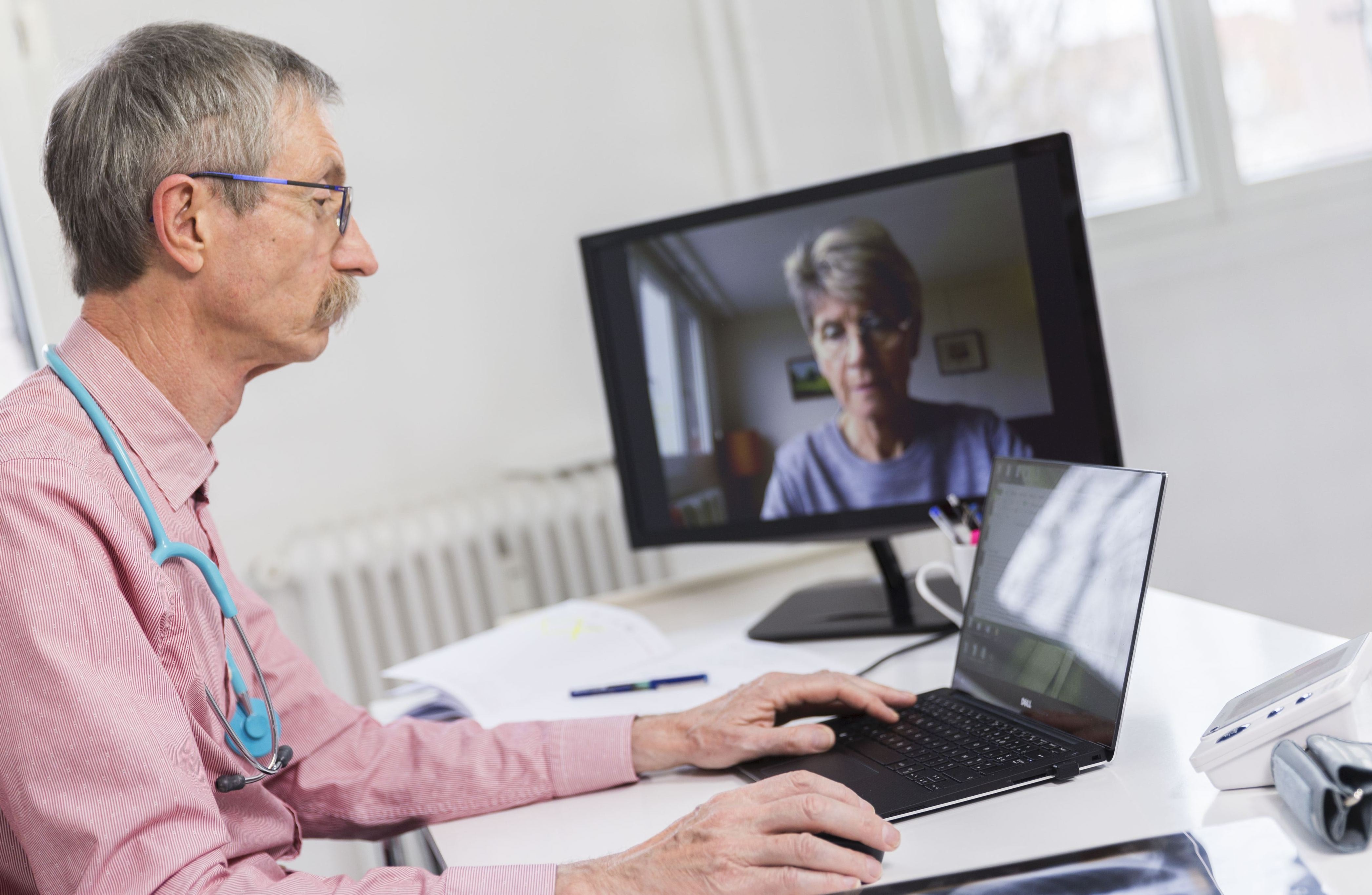 A white doctor talks to a white patient through his laptop.