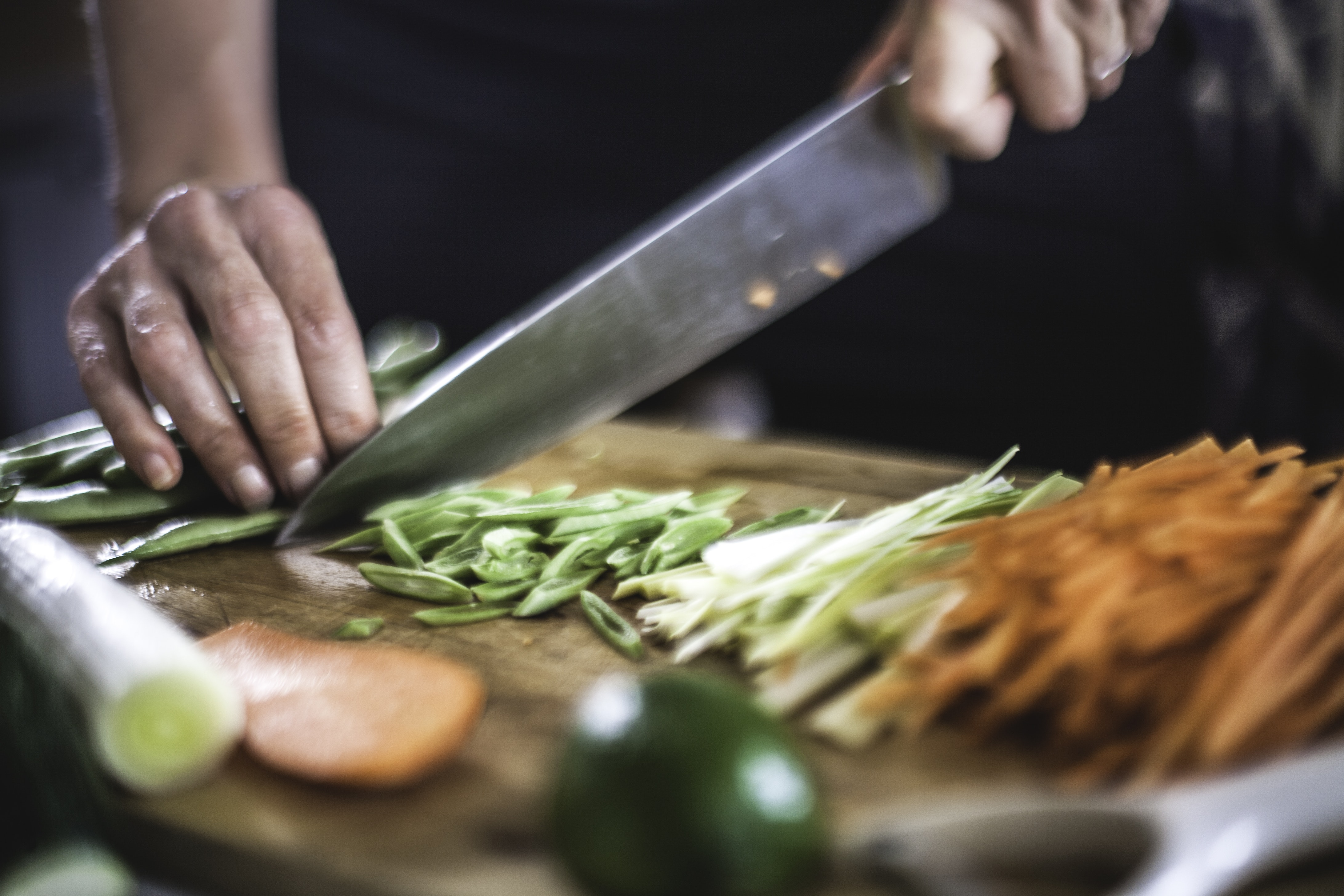 A cook cutting vegetables on a cutting board.