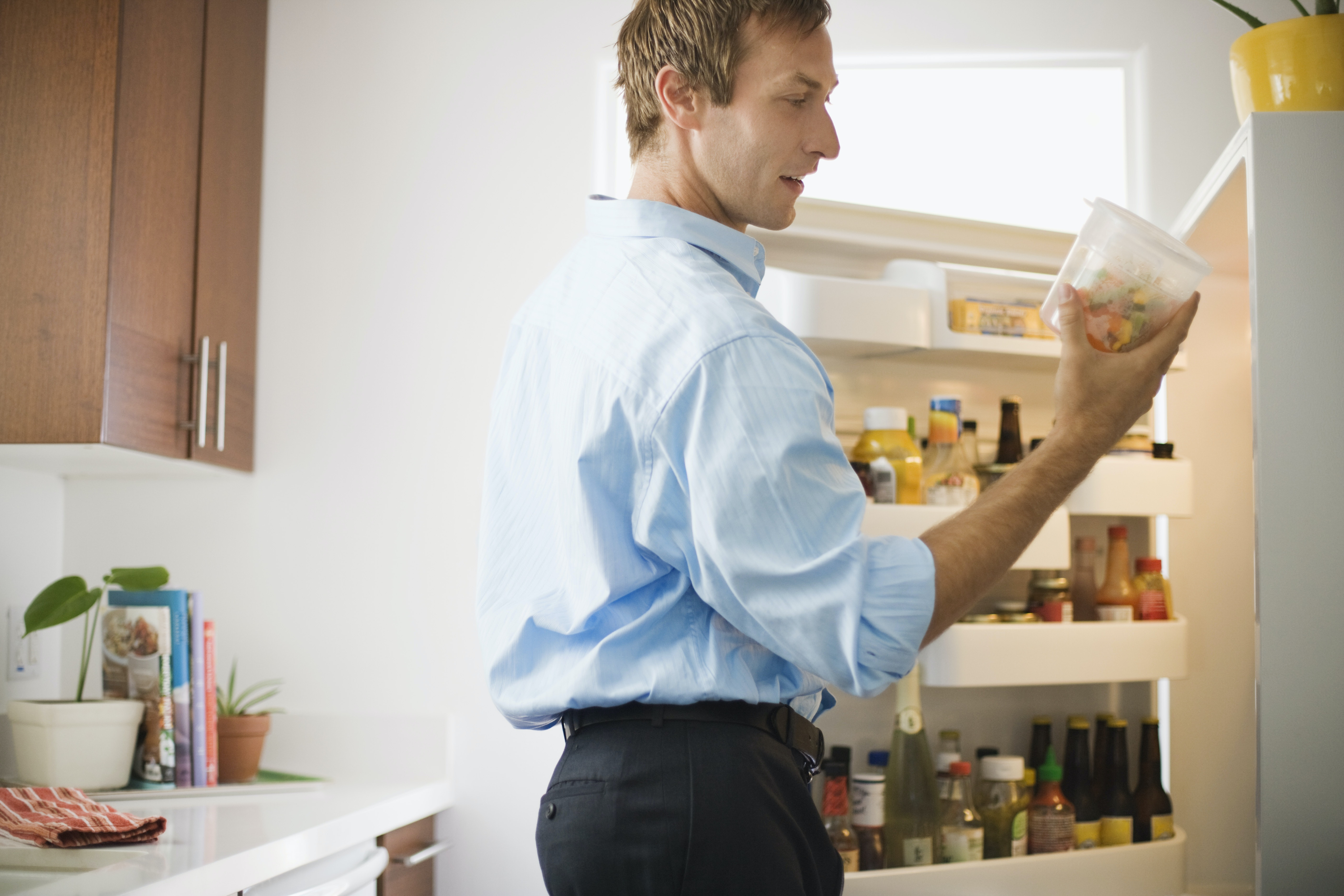 A man takes leftovers out of the refrigerator.
