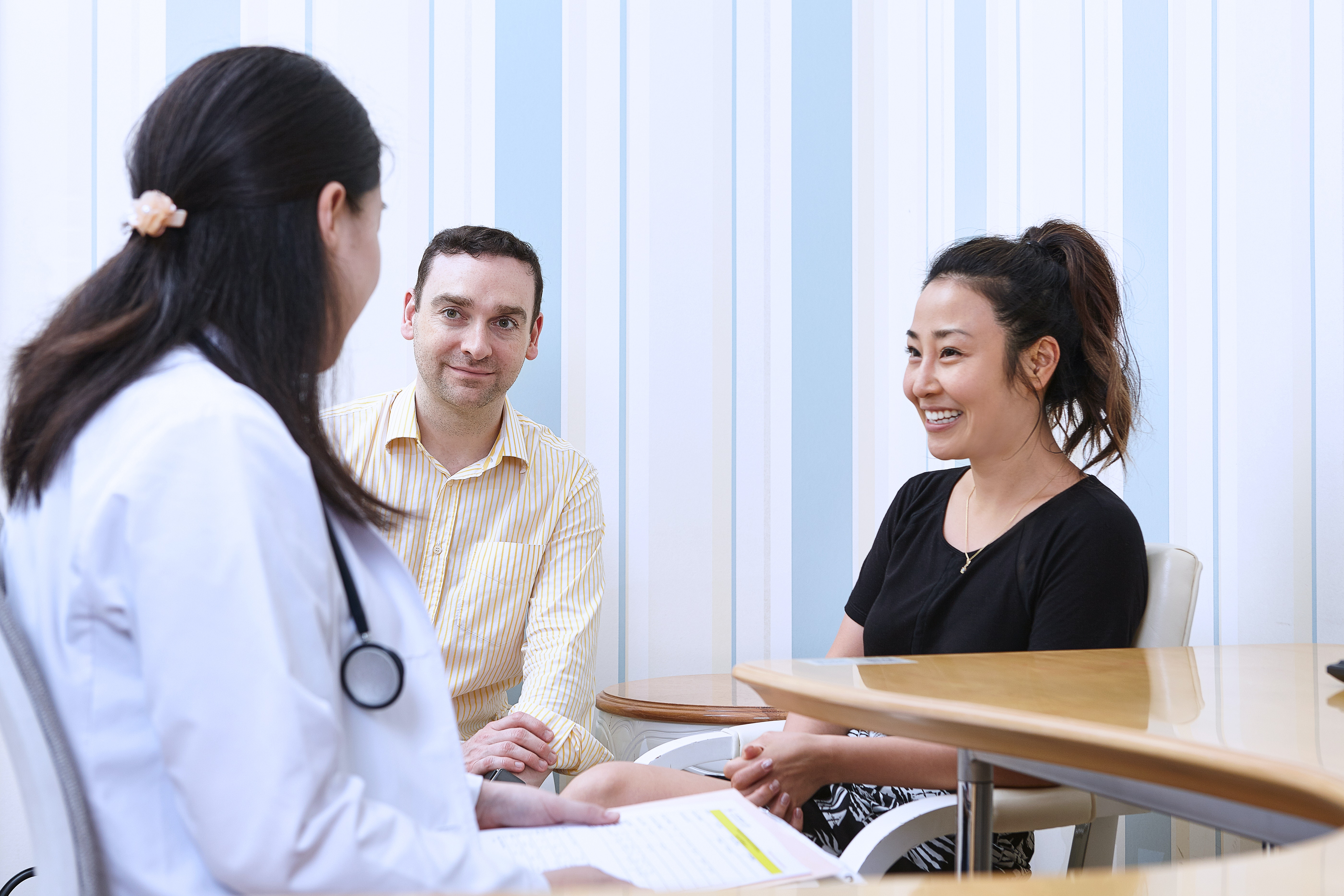 A medical professional sitting with a couple.