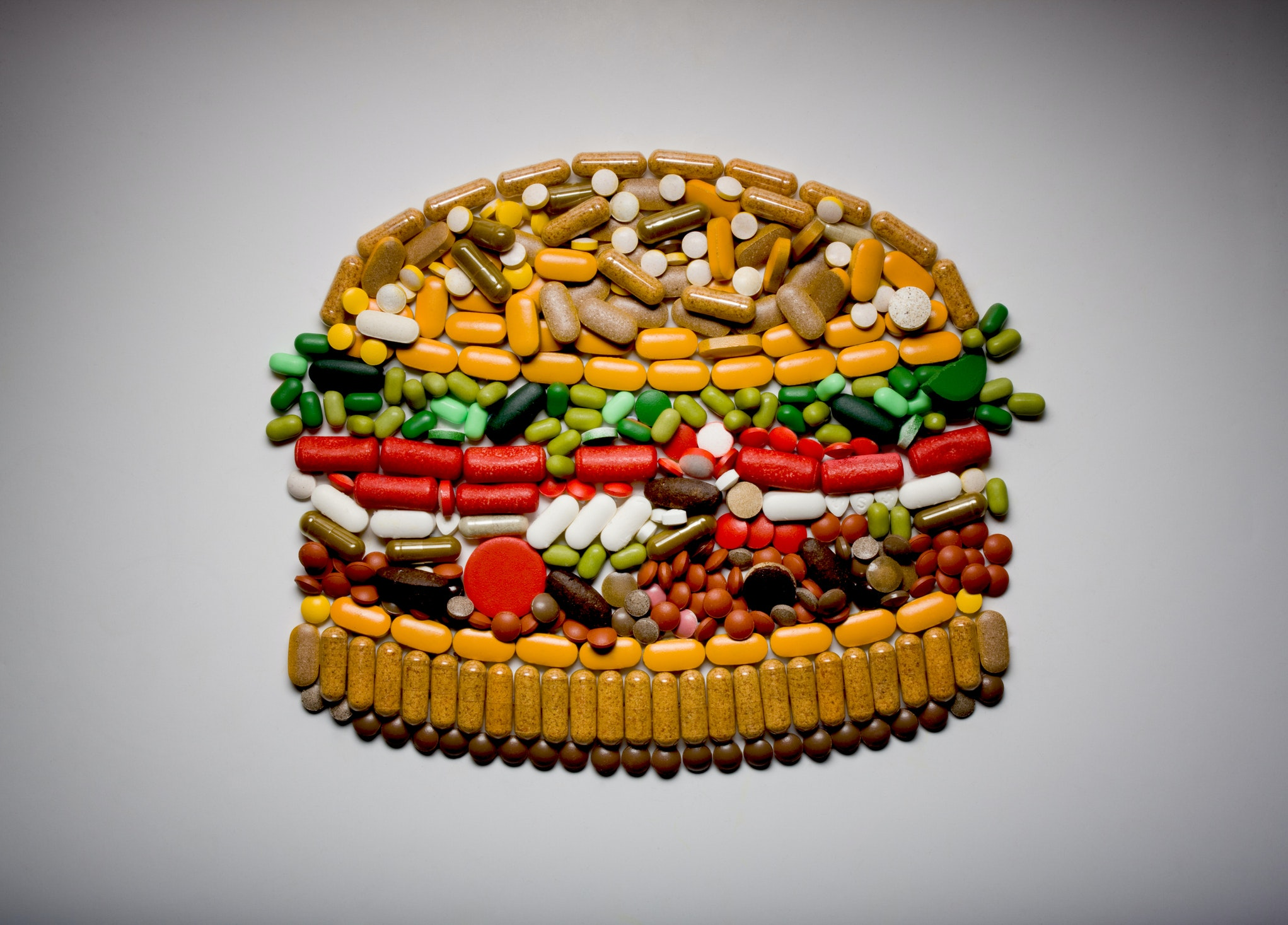 A collage of pills in the shape of a hamburger.
